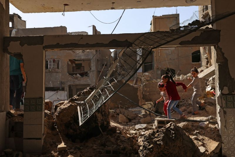 Palestinian children walk amid rubble in Gaza.