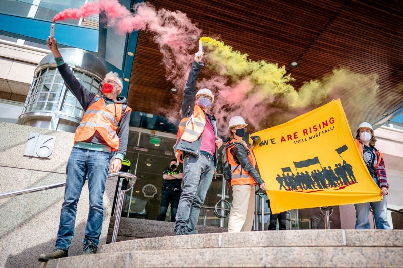 Protesters hold smoke flares as they take part in a demonstration organized by the global environmental movement Extinction Rebellion and the Dutch climate activist group Code Rood at the Shell headquarters in The Hague on May 18.
