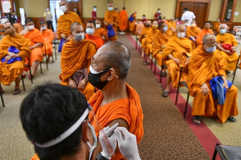 A Thai Buddhist monk gets a shot of Sinovac vaccine