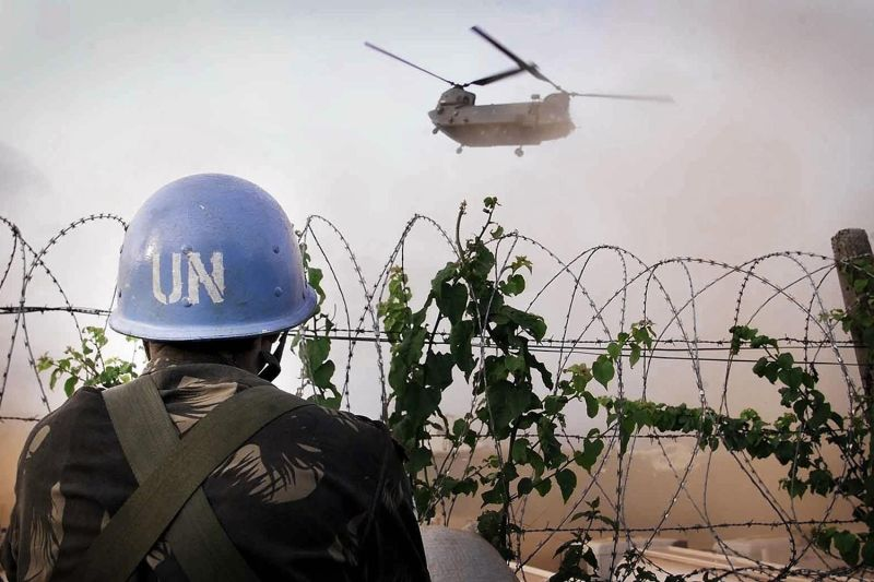 An Indian soldier watches a British Royal Air Force Chinook helicopter at the United Nations' headquarters in Freetown, Sierra Leone, on May 9, 2000.