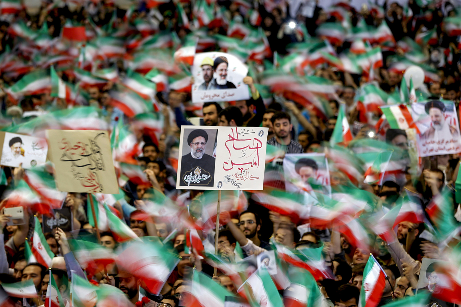 Supporters of Ebrahim Raisi wave flags