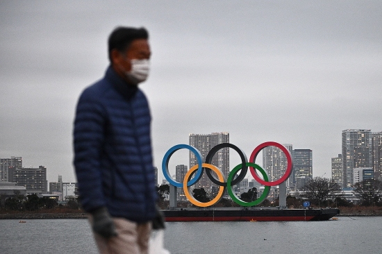 A man walks in front of the Olympic rings in Tokyo