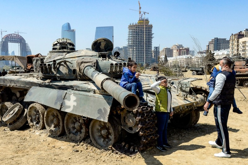A boy salutes in front of a tank in Azerbaijan