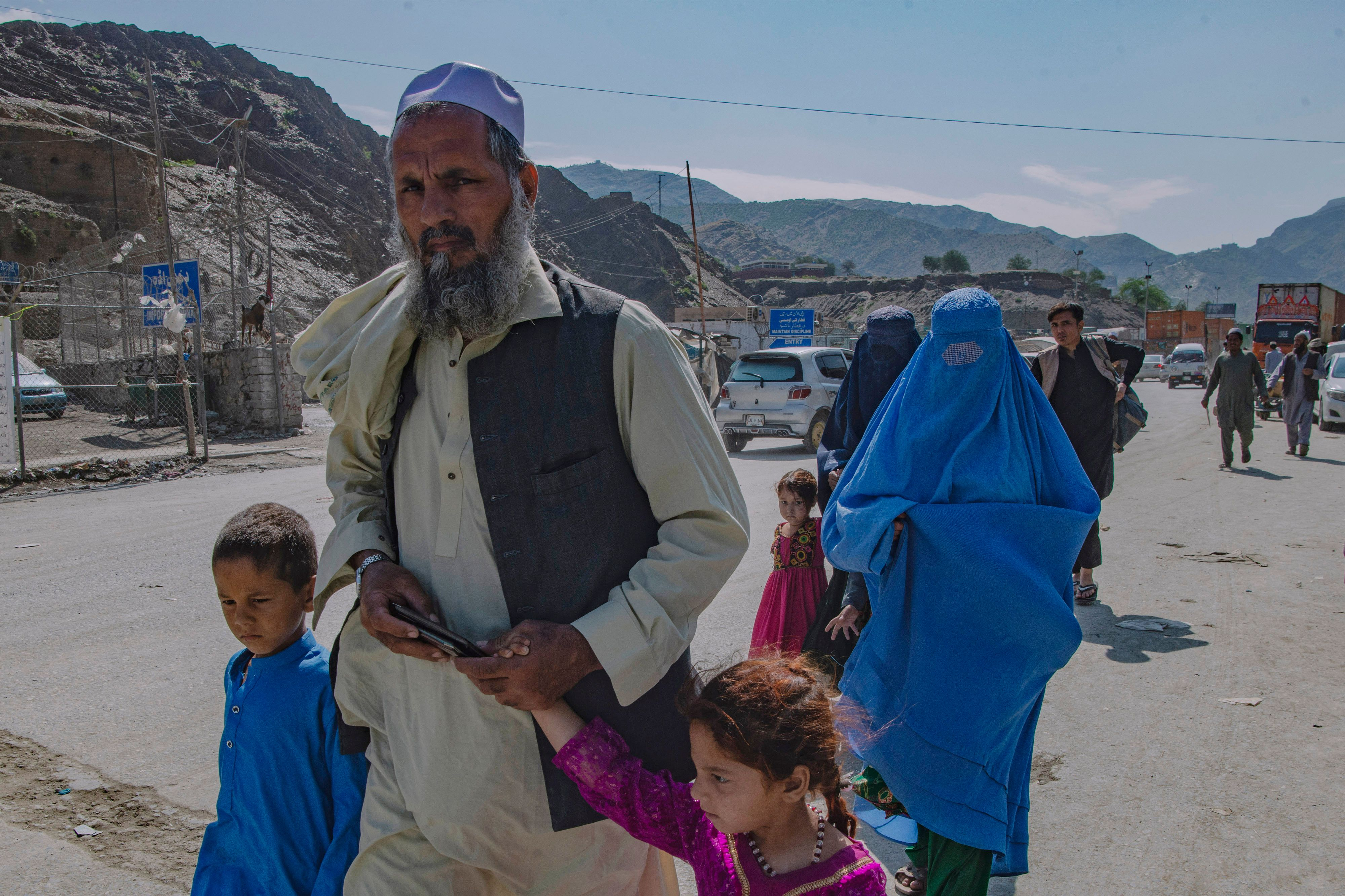 Afghan nationals make their way back across the Pakistan-Afghanistan land crossing border to Afghanistan in Torkham from Peshawar on May 5.