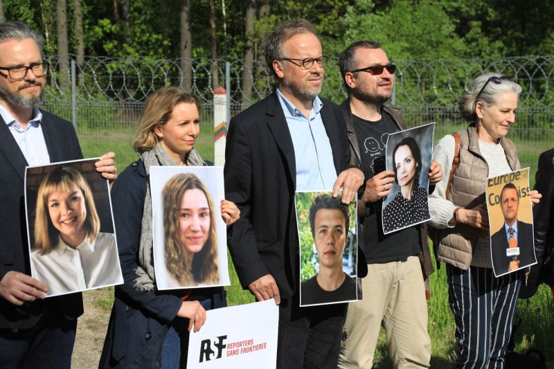 Protesters hold photos of detained Belarusian journalists