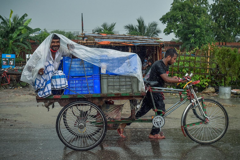 Man rides rickshaw in the rain in Bangladesh