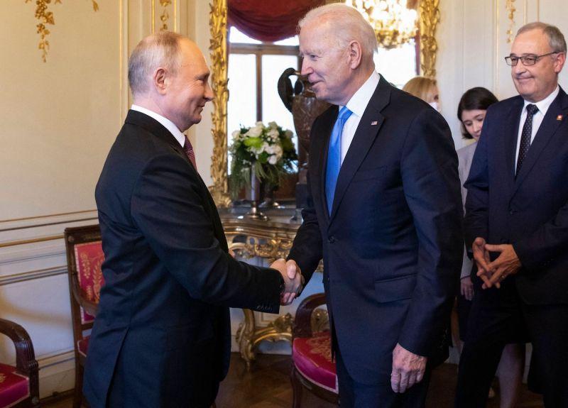 U.S. President Joe Biden shakes hands with Russian President Vladimir Putin.