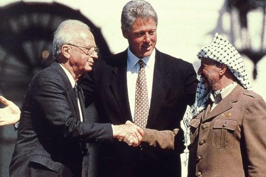 U.S. President Bill Clinton watches as Israeli Prime Minister Yitzhak Rabin and Palestinian leader Yasser Arafat shake hands