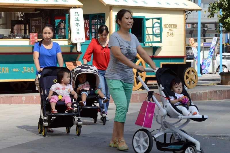 Chinese women take their babies for a stroll.