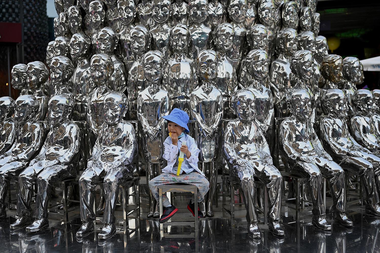 Boy sits on children sculpture in China