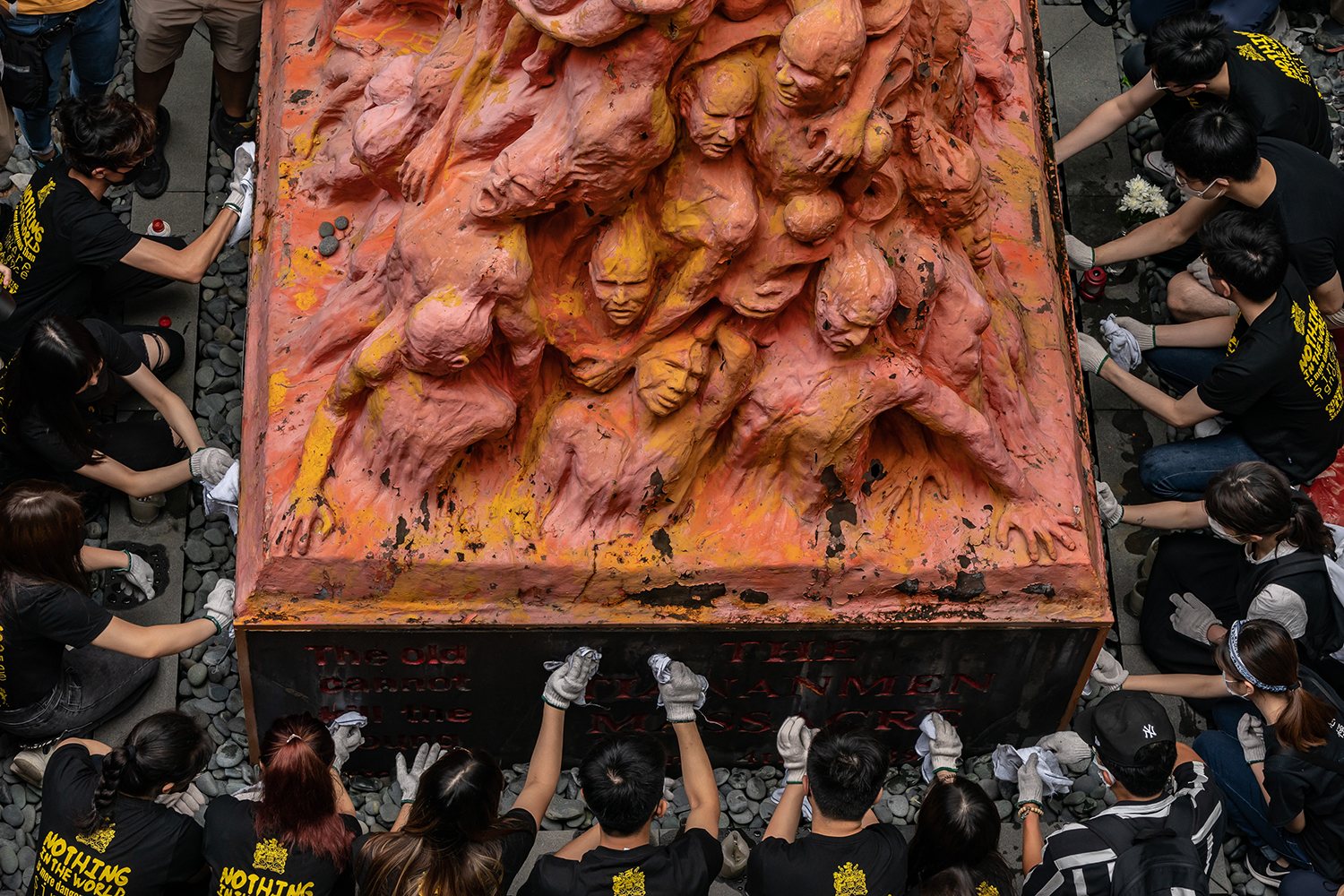 University students clean the Pillar of Shame sculpture in Hong Kong