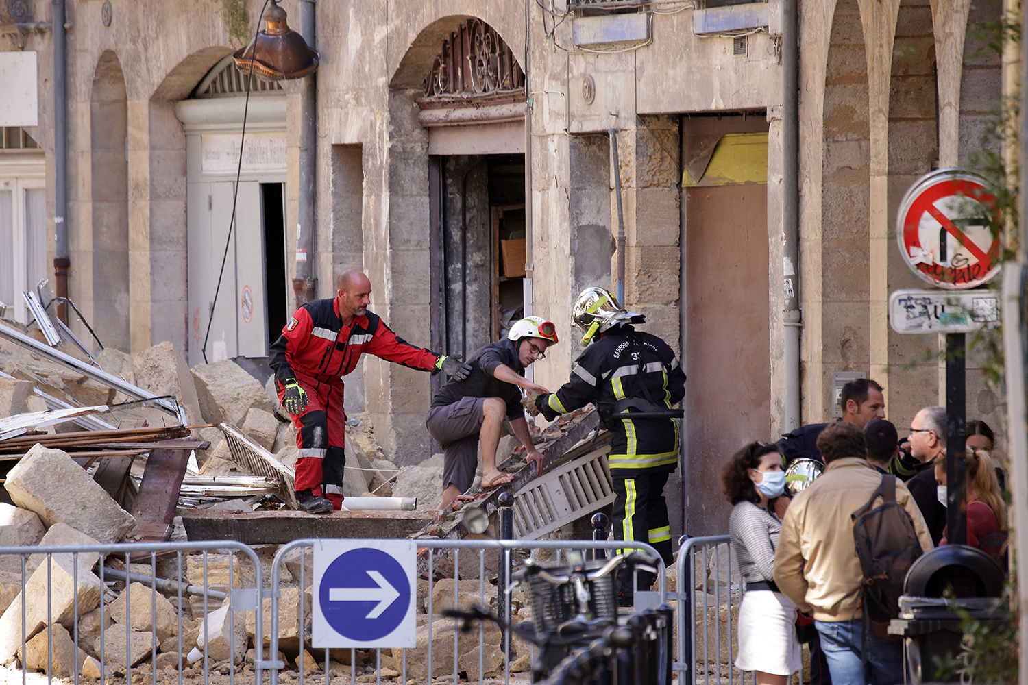 A person is evacuated by firefighters after a building collapsed in Bordeaux, France