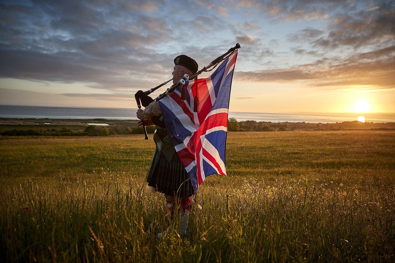 British piper plays at sunrise in France on D-Day anniversary