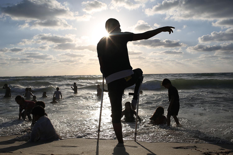An injured Palestinian man visits the Mediterranean seashore in Gaza City