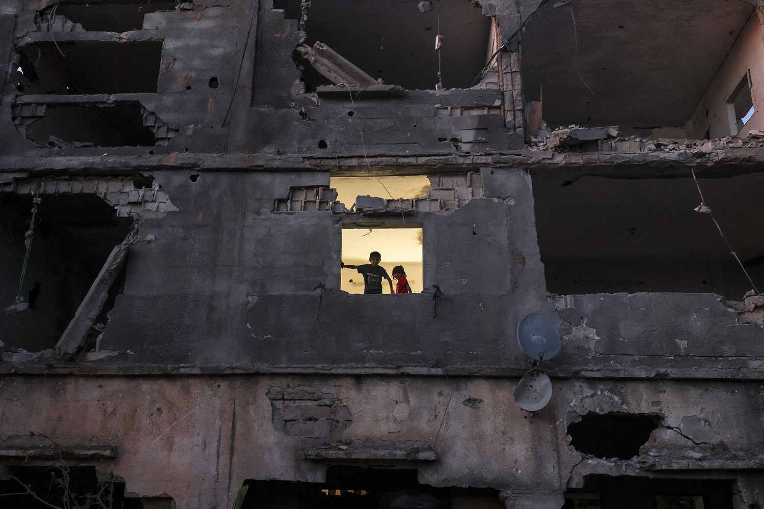 Palestinian children stand at the window of their damaged home.