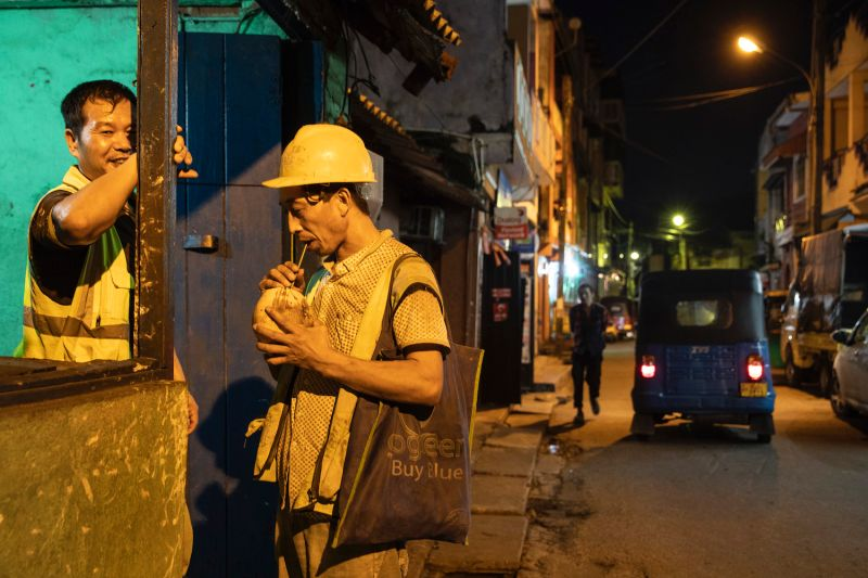 Chinese construction workers drink coconut juice.