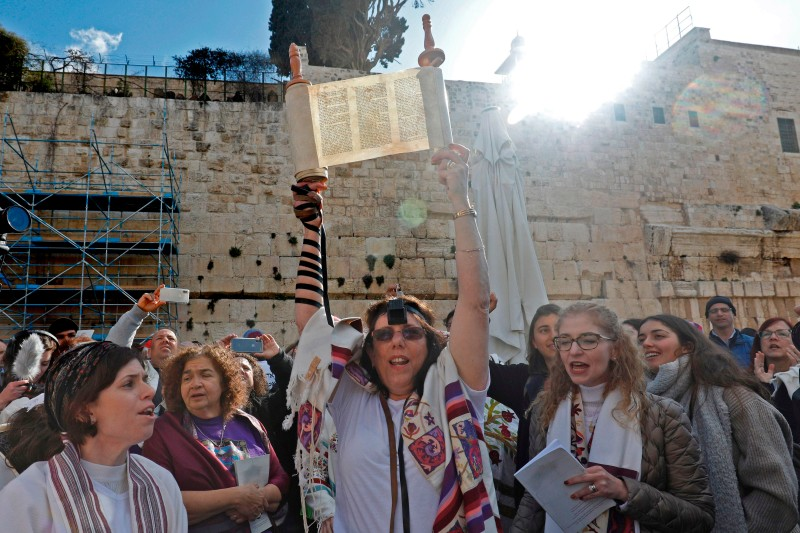 """A member of the liberal Jewish religious movement """"Women of the Wall"""" (WOW), wearing phylacteries and """"Tallit"""" traditional Jewish prayer shawls for men, holds up a Torah on March 8, 2019 at the Western Wall in the Old City of Jerusalem."""