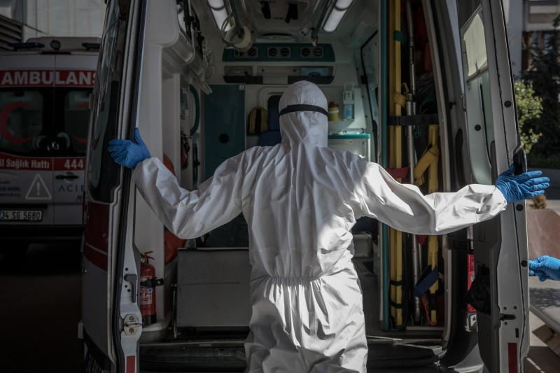 A medical worker closes an ambulance's doors.