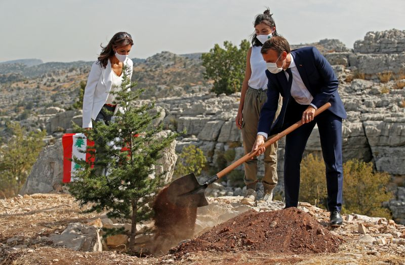 French President Emmanuel Macron plants a cedar tree alongside members of the NGO Jouzour Loubnan during a ceremony marking Lebanon's centenary in Jaj Cedars Reserve Forest, northeast of the capital Beirut, on Sept. 1, 2020.