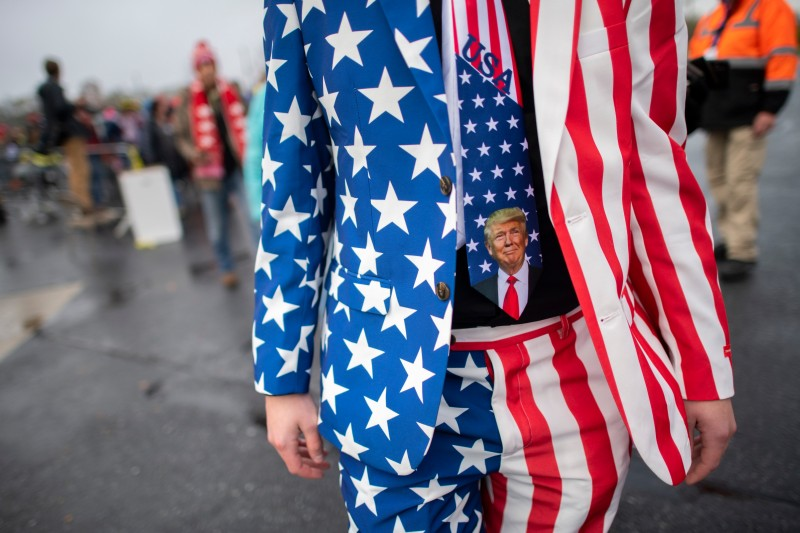 A man wearing a patriotic suit and Donald Trump themed tie joins supporters queueing before President Donald Trump holds a rally on Oct. 26, 2020 in Lititz, Pennsylvania.