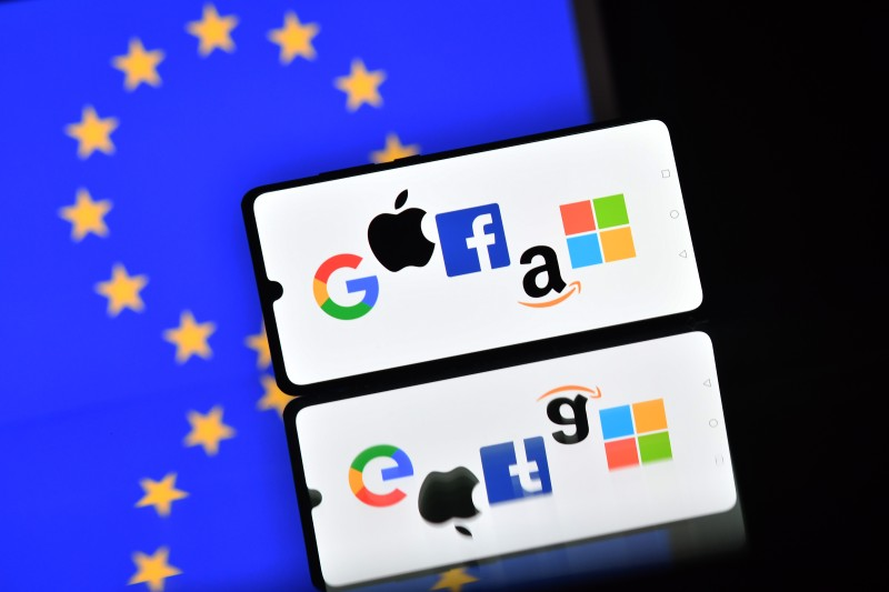 An illustration picture taken in London on December 18, 2020 shows the logos of Google, Apple, Facebook, Amazon and Microsoft displayed on a mobile phone with an EU flag displayed in the background.