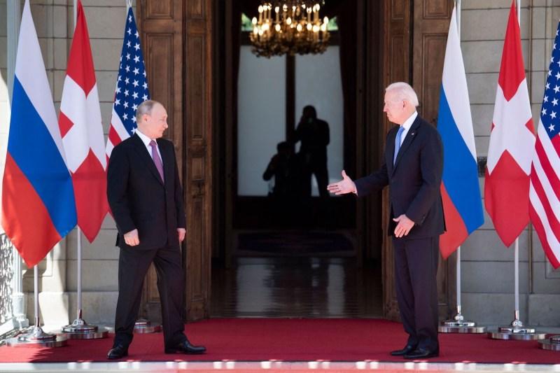 U.S. President Joe Biden prepares to shake hands with Russian President Vladimir Putin.