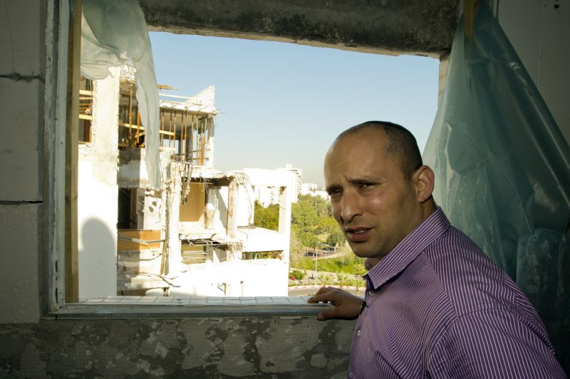 Naftali Bennett visits a building that was hit by a rocket, fired from Gaza, during a campaign visit in the city of Rishon Letzion, near Tel Aviv, on Jan. 21, 2013.