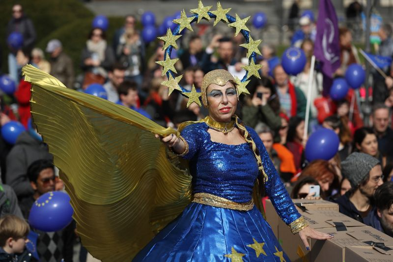"""A performer on stilts dressed in the colors of the flag of the European Union attends a """"March for Europe"""" gathering to celebrate the 60th anniversary of the Treaty of Rome, which created the precursor to the European Union, on March 25, 2017 in Berlin, Germany."""