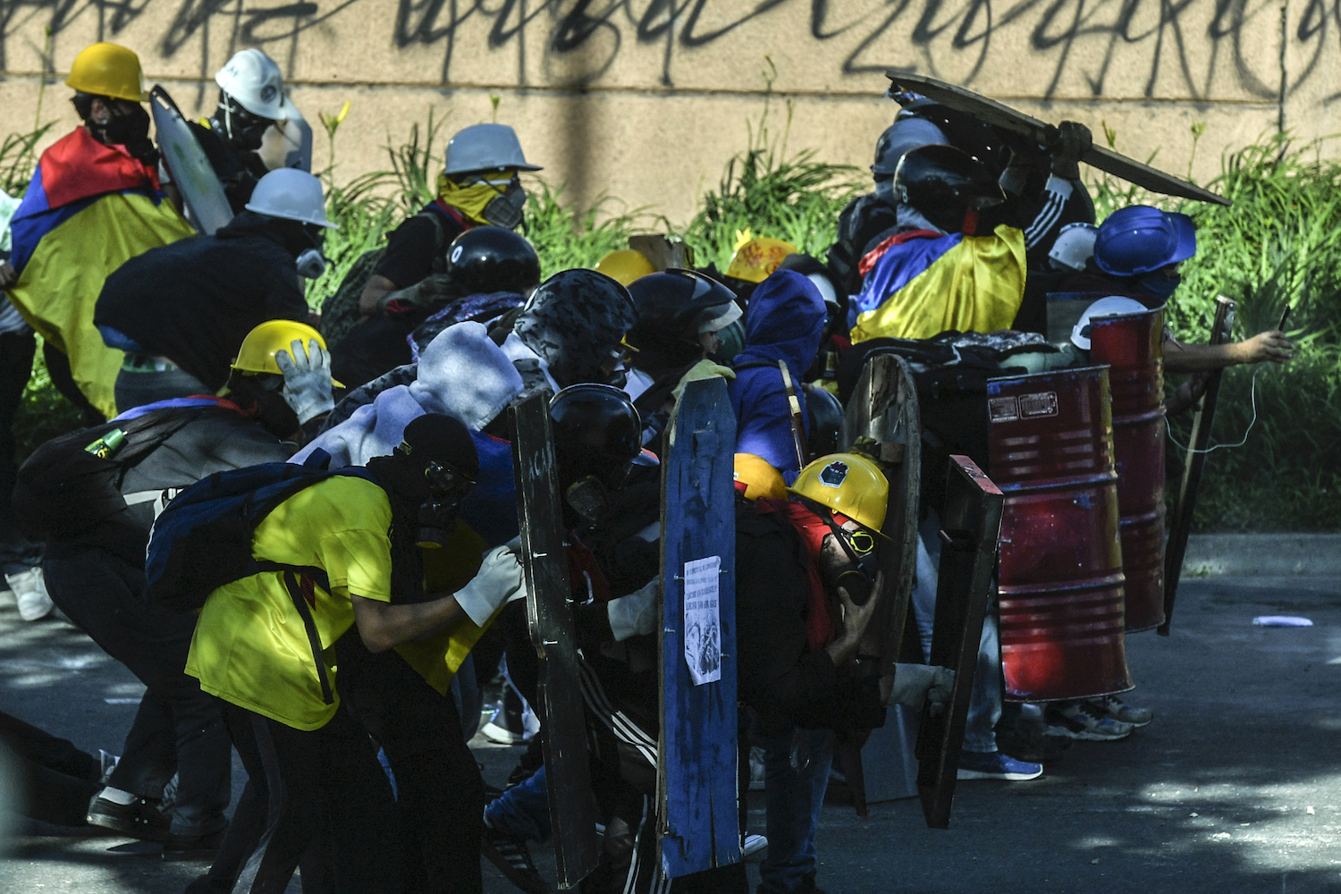 Demonstrators use makeshift shields as they clash with riot police during a new protest against the government in Medellin, Colombia, on June 16.