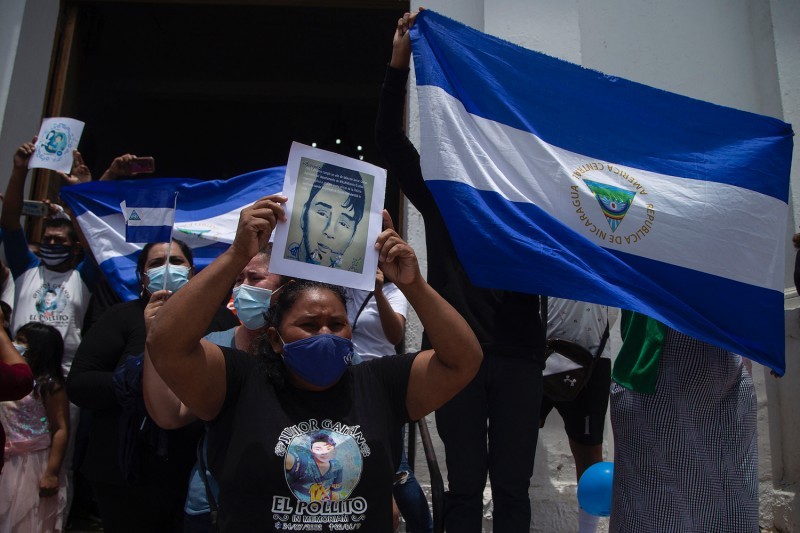 People hold Nicaraguan flags and shout slogans outside the Church of San Miguel in the Nicaraguan town of Masaya, during a mass to commemorate the third anniversary of the beginning of the protests against the government of President Daniel Ortega, on April 18.