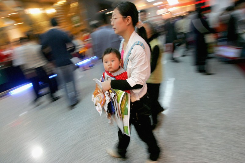 A woman holding a baby and leaflets visits a real estate fair in Chengdu, China, on April 21, 2005.