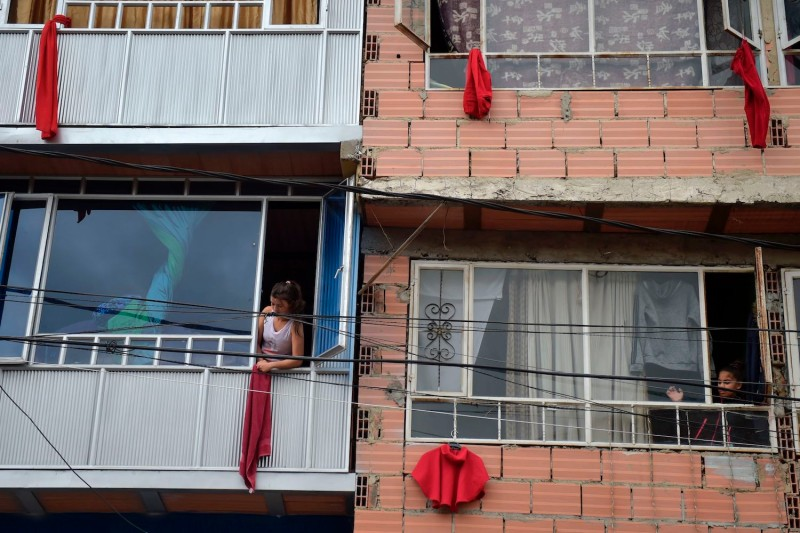 Residents hang red rags in their windows as a distress signals for government aid during the COVID-19 pandemic in Bogota on May 13, 2020.