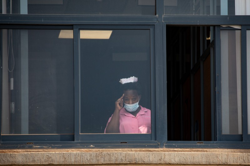 A health care worker salutes from a window of the Mulago National Referral Hospital on the first day of the country's vaccination rollout after it received the first batch of AstraZeneca doses in Kampala, Uganda, on March 10.