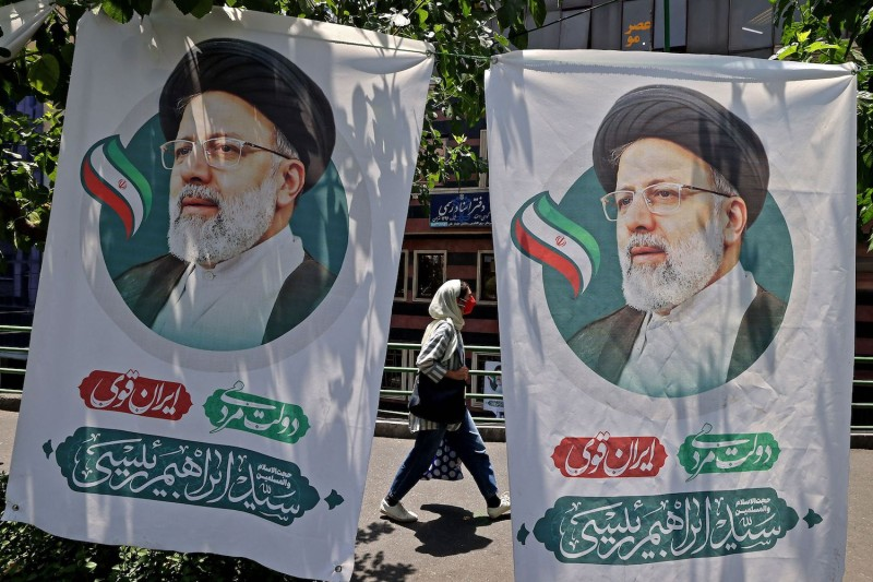 An Iranian woman walks past banners of ultraconservative cleric and presidential candidate Ebrahim Raisi in Tehran, Iran, on June 17.