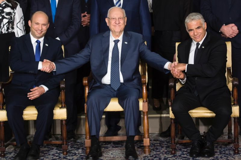 Israeli President Reuven Rivlin sits between Israeli Prime Minster Naftali Bennett (left) and Foreign Minister Yair Lapid as they pose for a group photo in Jerusalem on June 14.