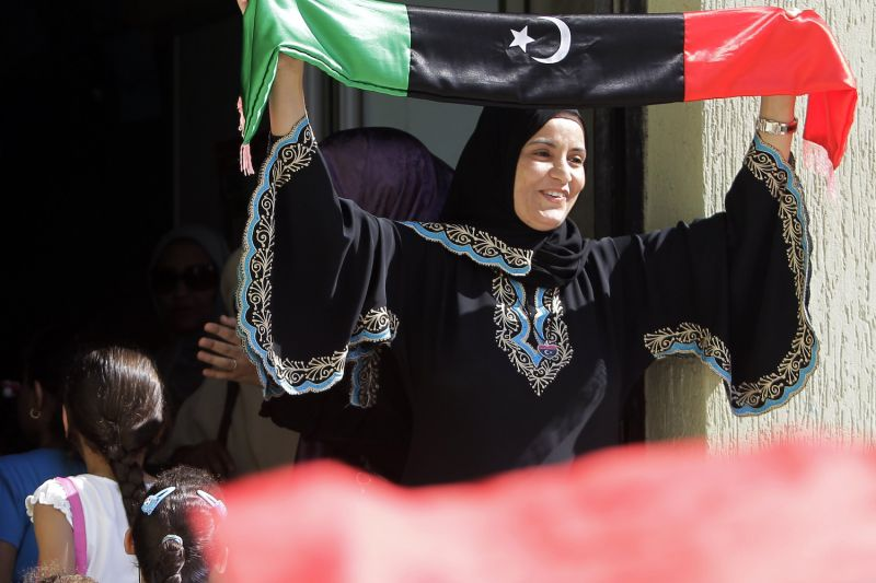 A Libyan teacher waves the flag of Libya's former monarchy, which was adopted by anti-Muammar al-Qaddafi forces, at the start of the school year in Tripoli on Sept. 18, 2011.