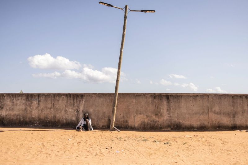 A man rests against a wall of a sports stadium in Pemba, Mozambique, on May 22. The sports stadium is used as a transit camp for internally displaced persons fleeing attacks in the north of the country.