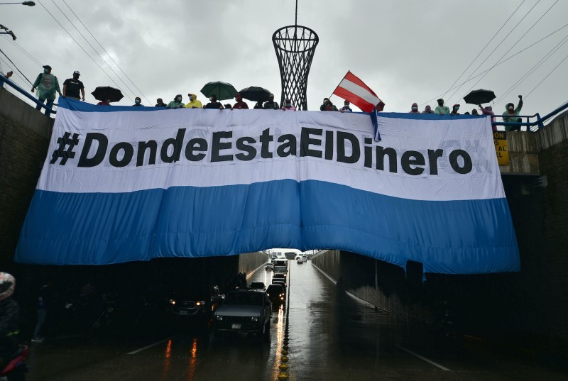 Protesters in Honduras hold banners.