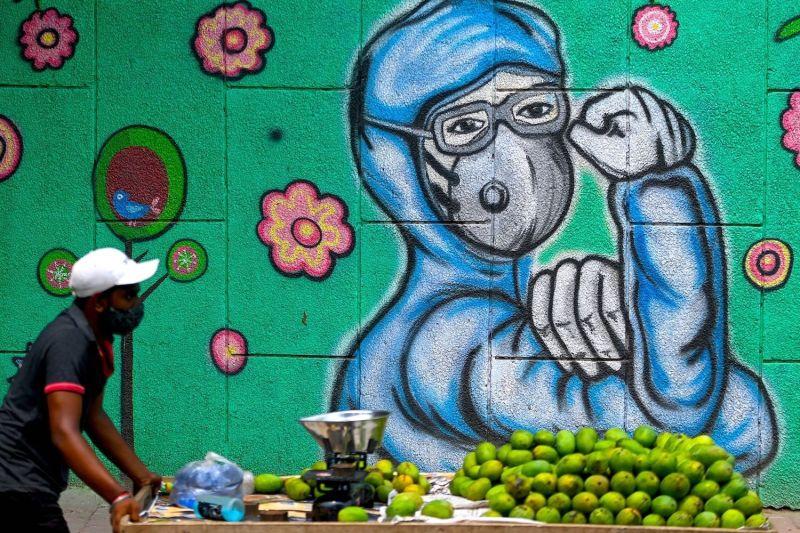 A fruit vendor walks by a COVID-19 mural.