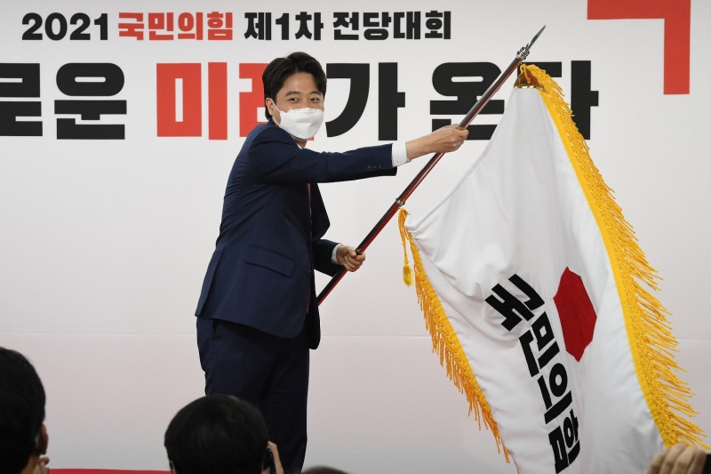 Political leader Lee Jun-seok waves the People Power Party's flag.