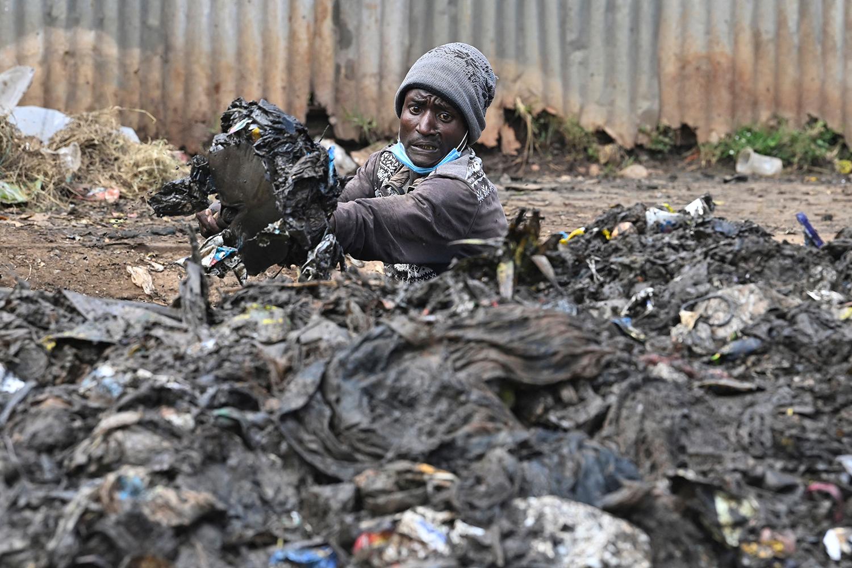 A Kenyan environment activist unclogs a drain