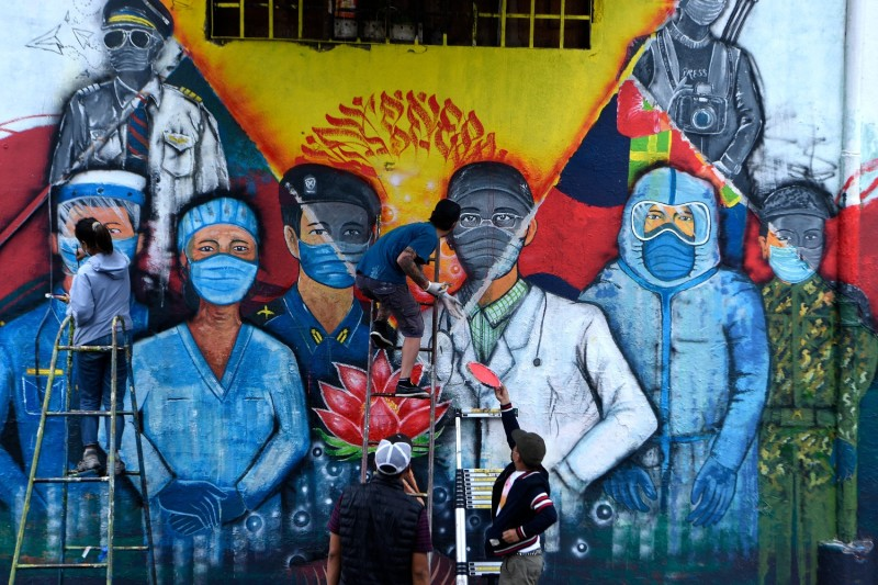 Street artists paint a mural depicting COVID-19 front-line workers in Nepal.