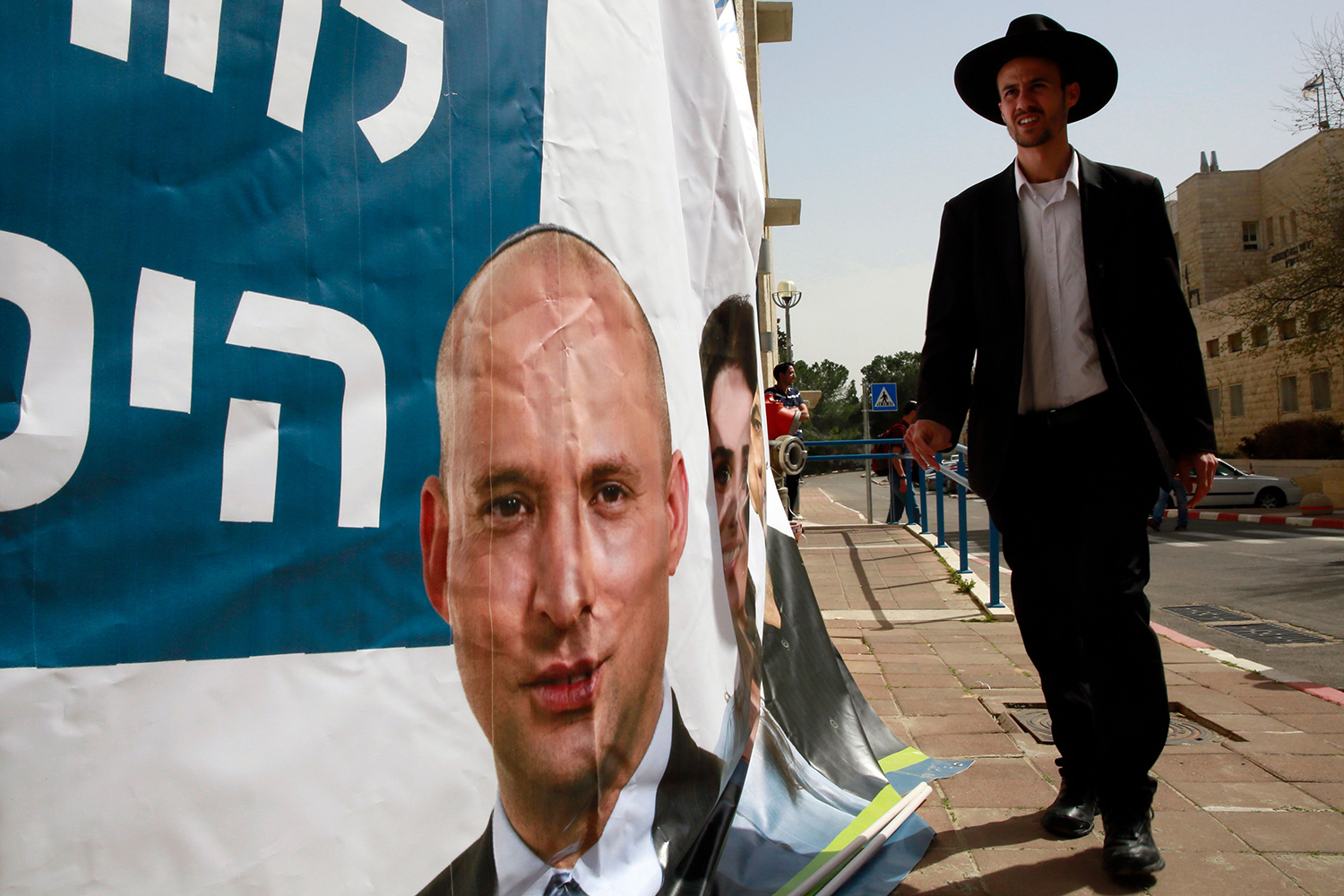 An Israeli man walks past an election campaign poster for Bennett, as he heads to Bennett's electoral rally in Jerusalem on March 8, 2015.