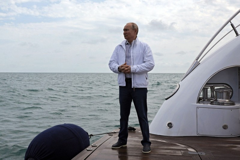 Russian President Vladimir Putin stands on a boat.