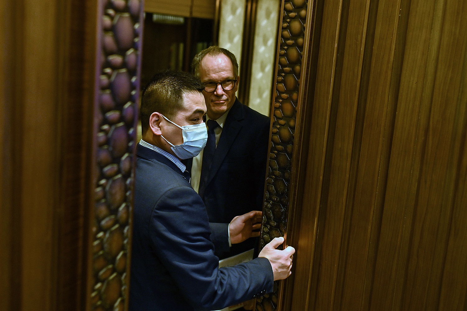 Peter Ben Embarek (right) leaves a press conference after wrapping up a visit by the international team of experts from the World Health Organization in Wuhan, China, on Feb. 9.