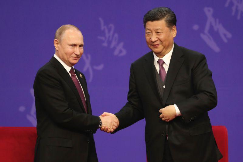 Putin and Xi shake hands.