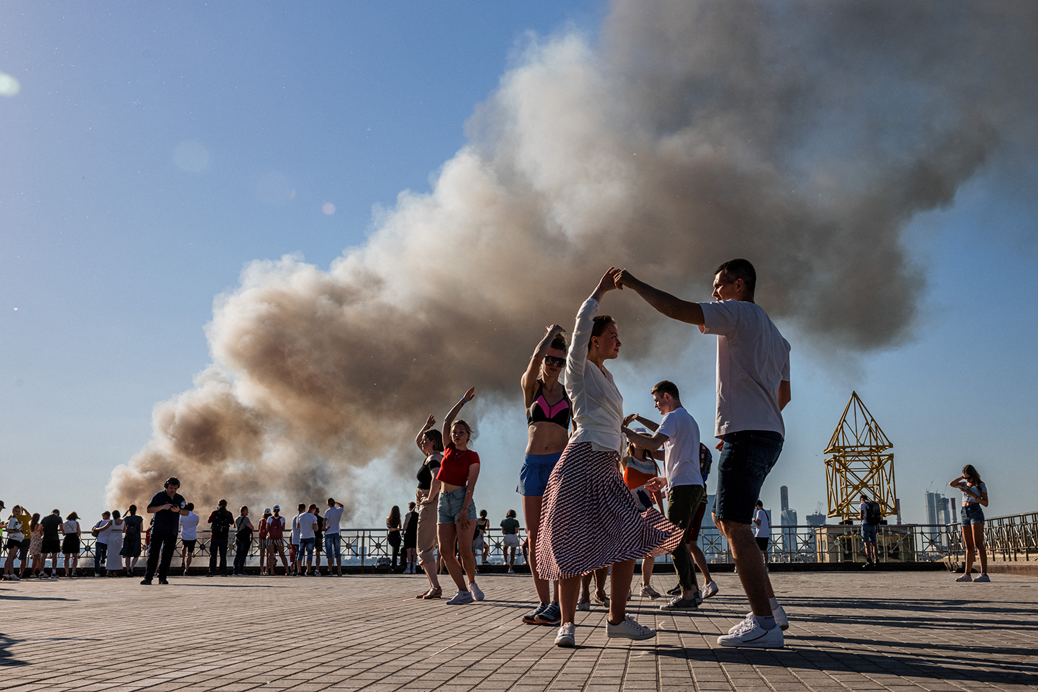 Russians dance as building burns behind them