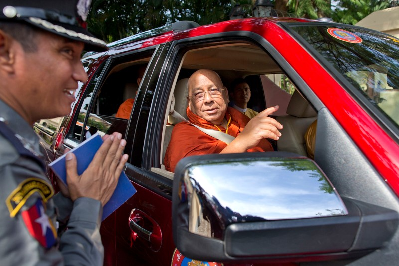 A policeman at the entrance to the archbishop's house greets the prominent Buddhist monk Sitagu Sayadaw