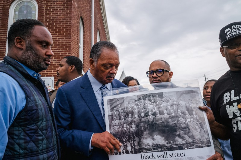 """Community residents look at a poster of """"Black Wall Street"""" in Tulsa."""