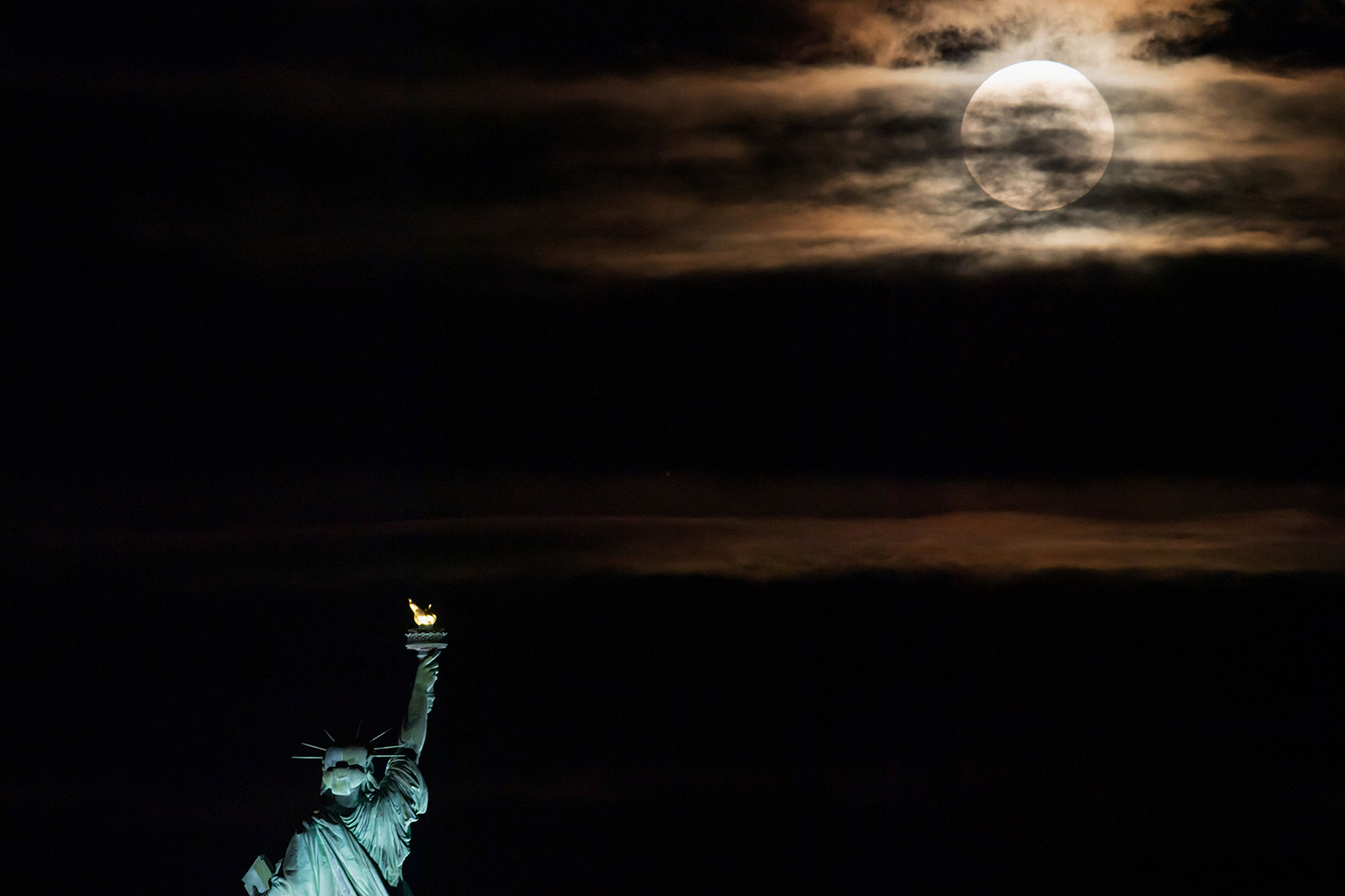 The moon rises behind the Statue of Liberty in New York